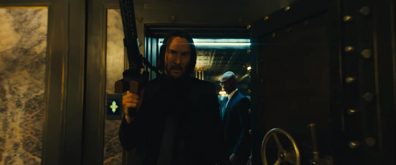 John's black suit at The Continental with Charon in the background (Image Credits: Summit Entertainment / Lionsgate)