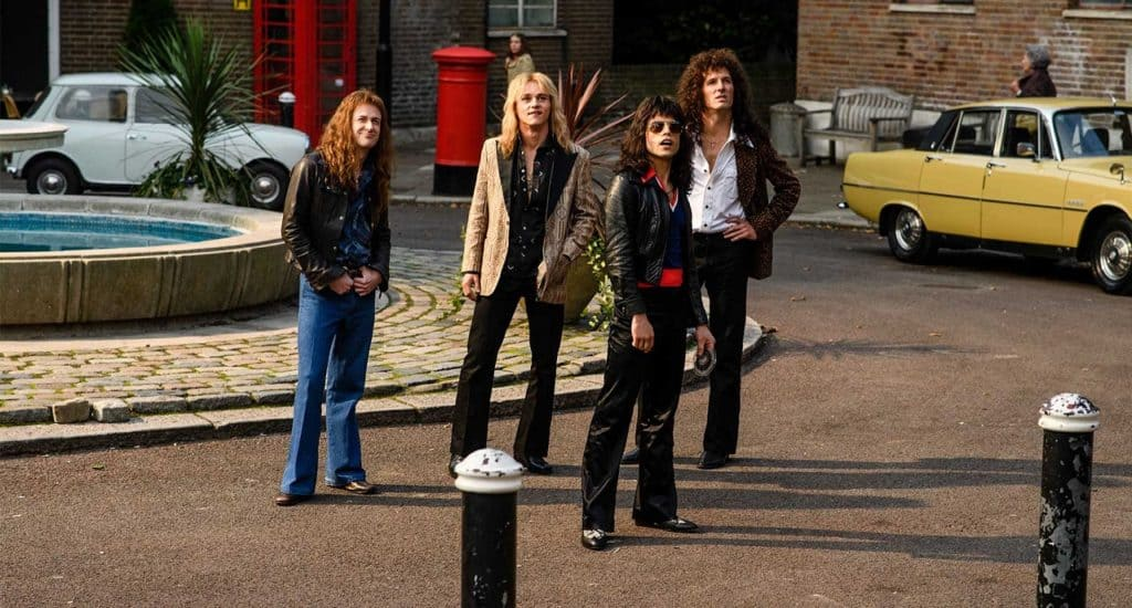 A scene where the members of Queen supposedly throw a rock through a fictional EMI execs window for not believing in Bohemian Rhapsody's success (Image Credits: 20th Century Fox)